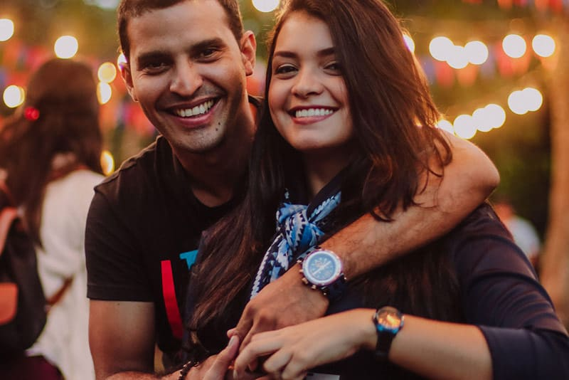 couple hugging and holding hands in front of festival lights