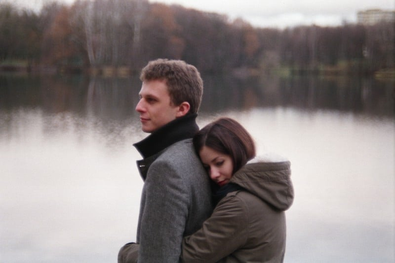 woman hugging man from behind near water