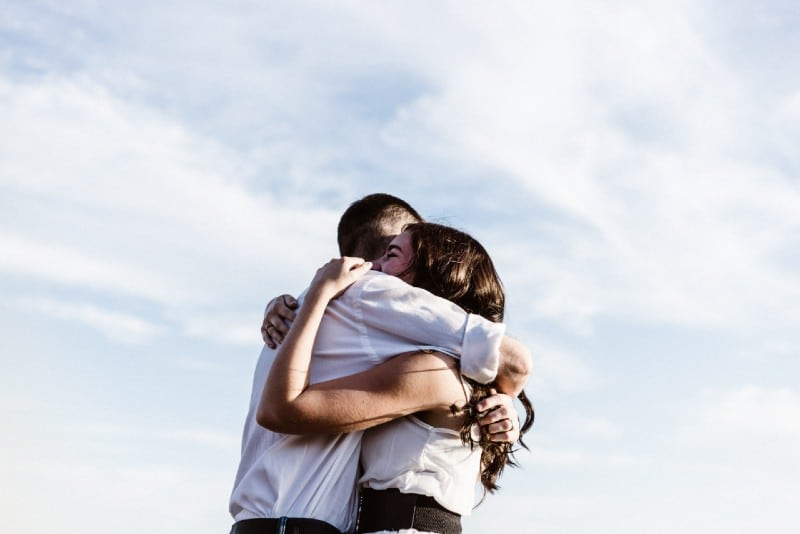 man in white shirt hugging woman outdoor