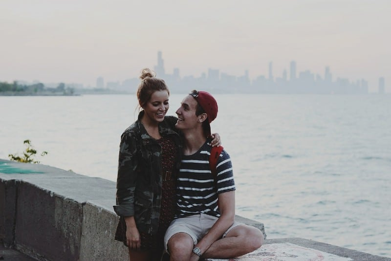 woman with hair bun and man in striped shirt smiling