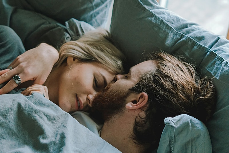 Couple in bed man kisses woman's forehead