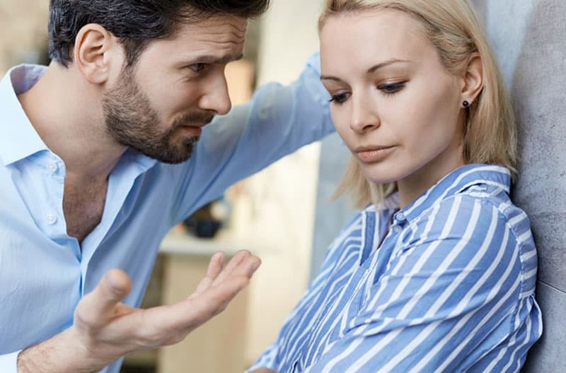 couple in blue top man explaining near woman leaning on the wall