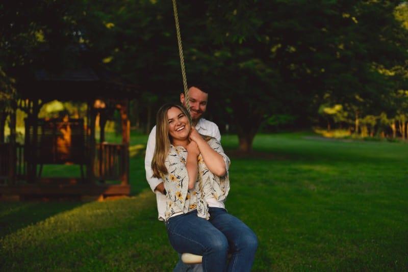 man standing behind smiling woman on swing