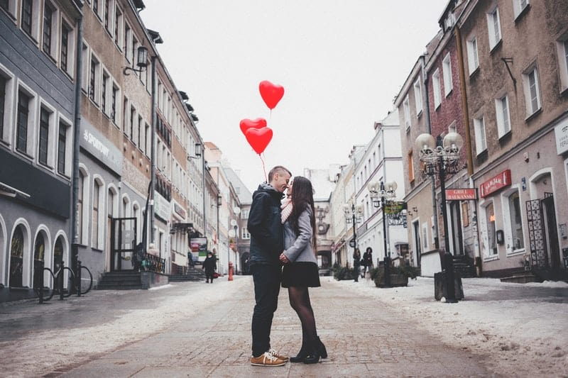 couple in the middle of the street kissing and carrying red heart balloons