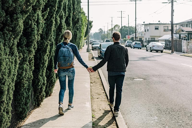 Couple wearing jeans holding hands while walking on the street