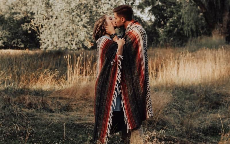 Romantic couple kissing while standing under a pillow in the forest