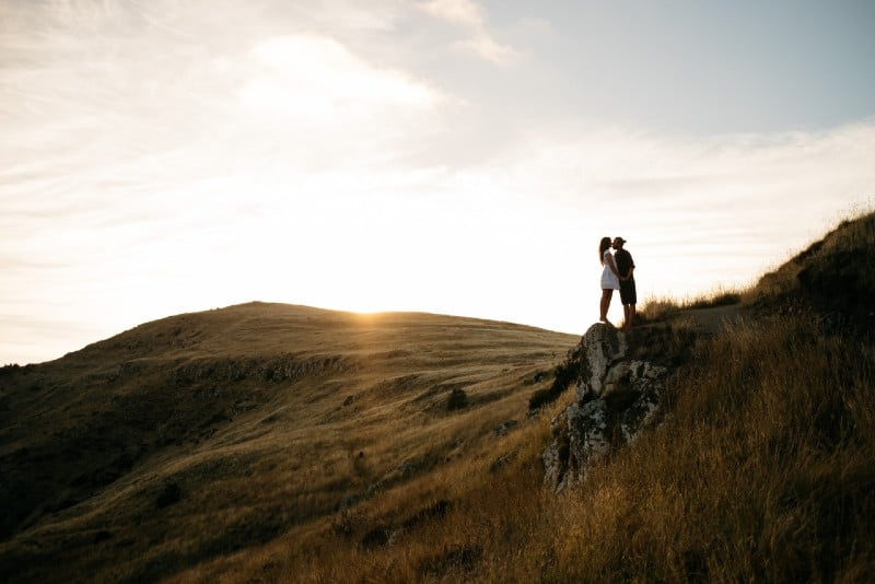 man and woman in white dress kissing on top of hill