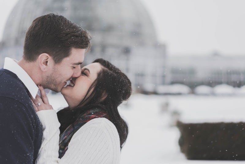 man and woman kissing and smiling on snow