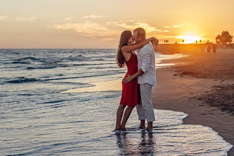 couple kissing on sunset while standing in the ocean