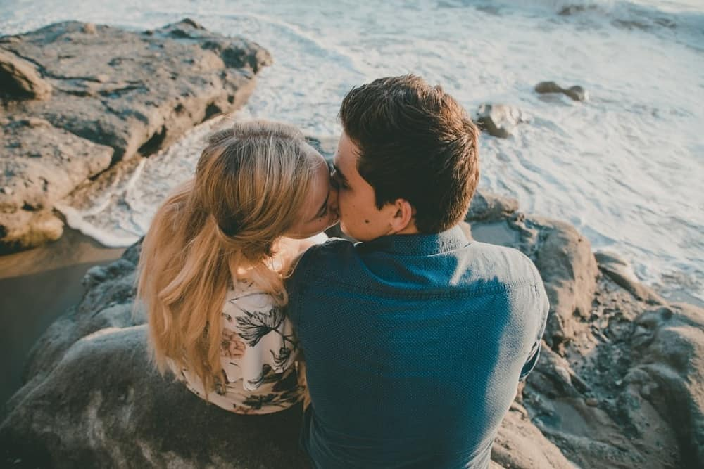 couple kissing while sitting on the rock