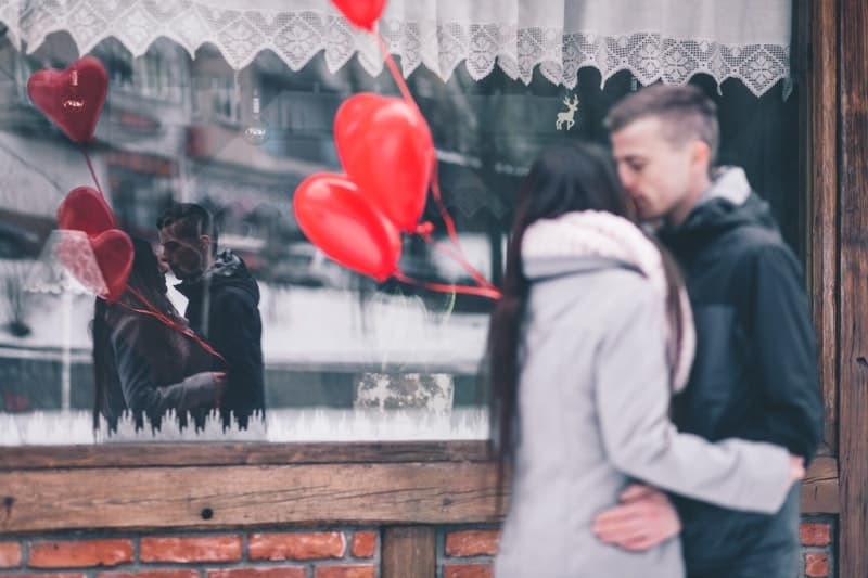 couple kissing with balloon colored red with reflection on a shop window