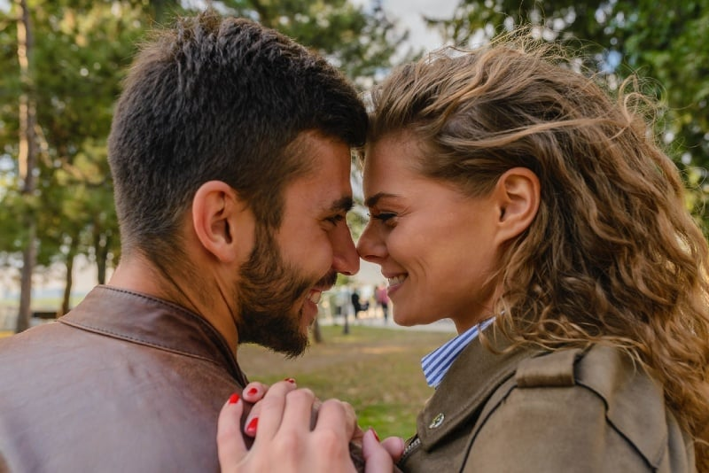 man wearing brown leather jacket looking at woman