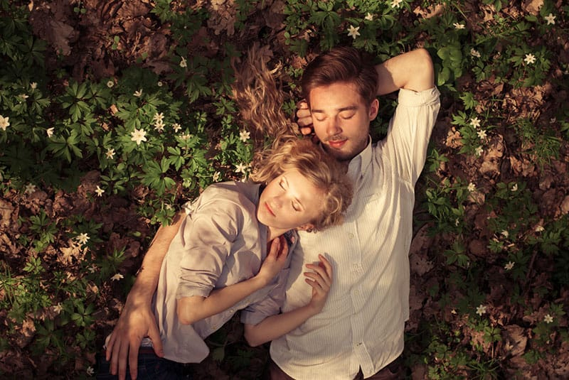 couple lying in nature on the ground