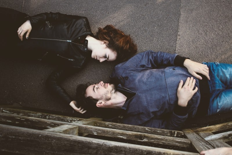 man and woman lying on concrete making eye contact