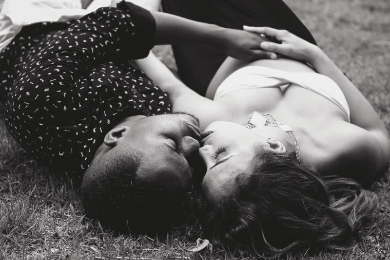 man and woman facing each other and lying on grass