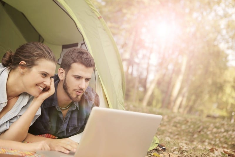 man and woman lying on tent and using laptop