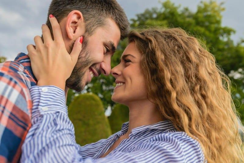 woman in striped shirt touching man's face