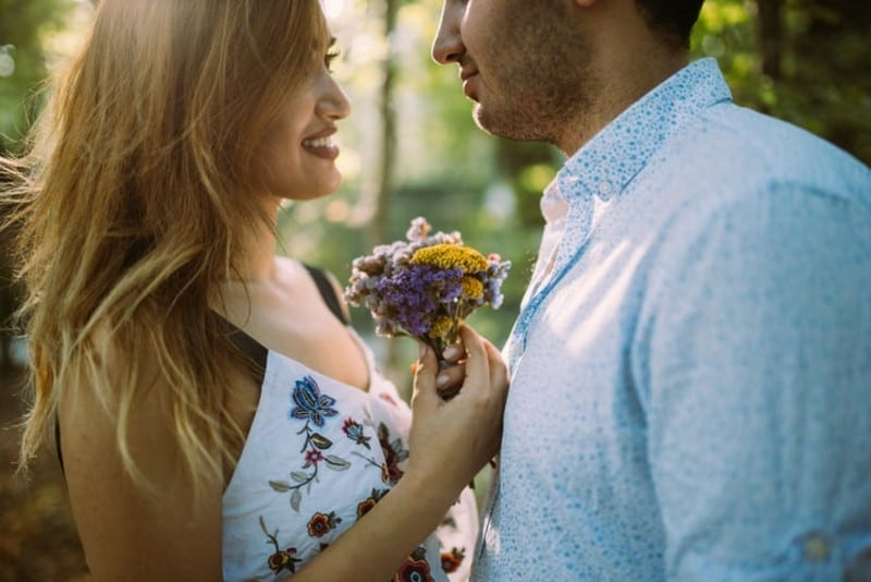 woman with flowers and man making eye contact outdoor