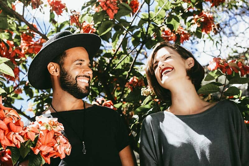 Couple by the flowering tree man wearing hat with grinning woman