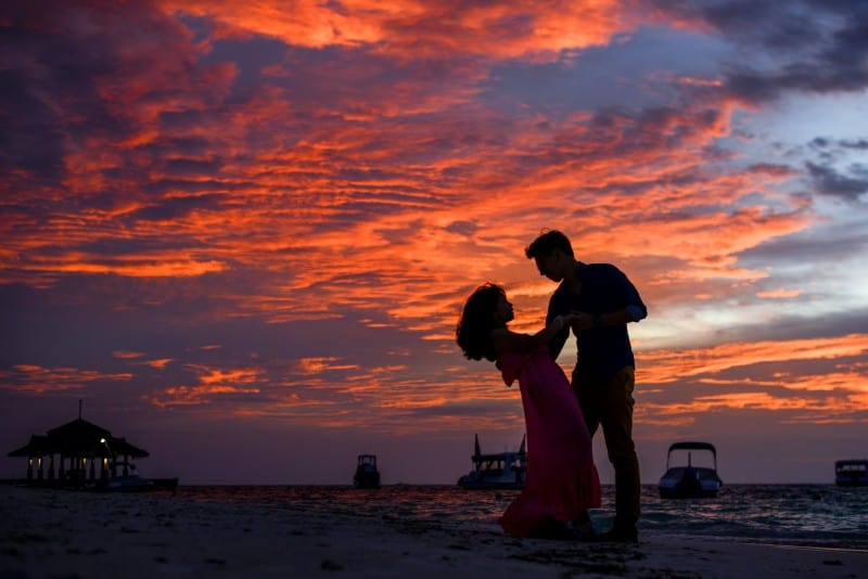 man and woman holding hands on beach during sunset