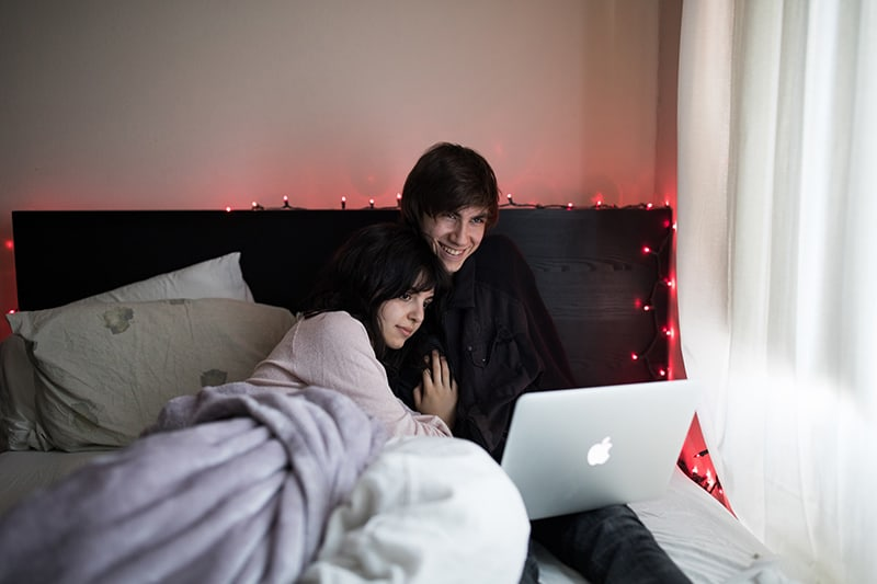 couple on bed using MacBook beside of window with white curtain