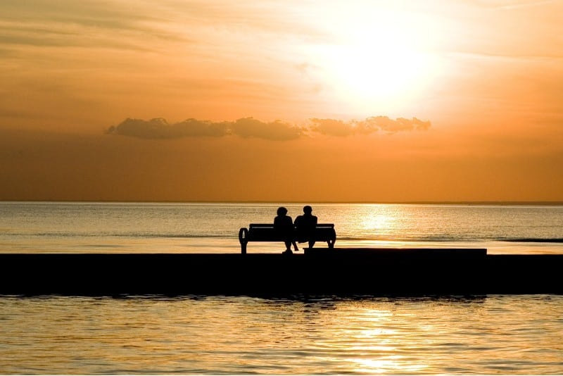 man and woman sitting on bench and watching sunset