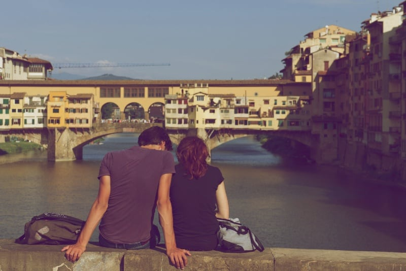 man and woman sitting on bridge looking at river