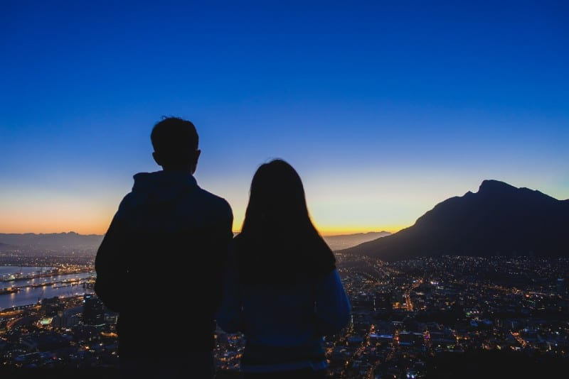 man and woman standing on hilltop and watching city