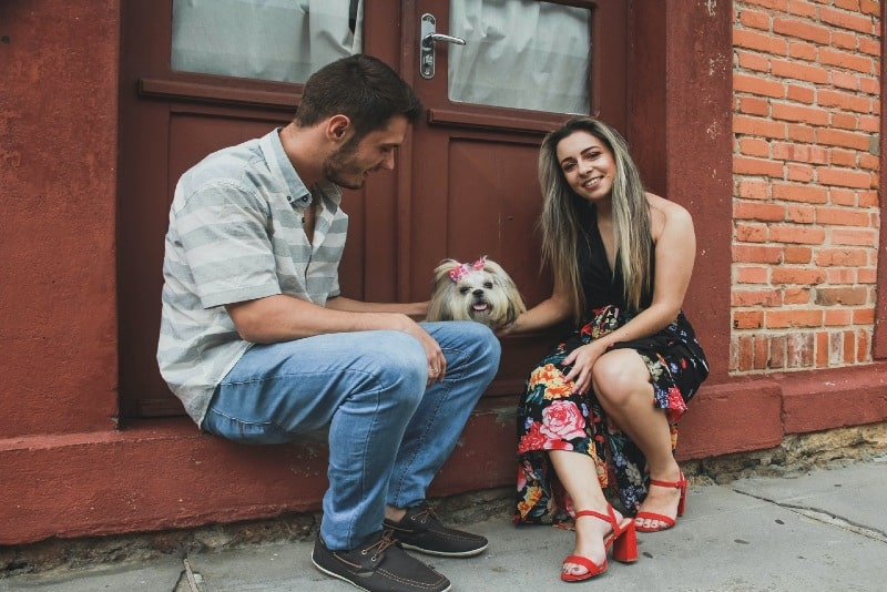 man and woman sitting near door and petting dog