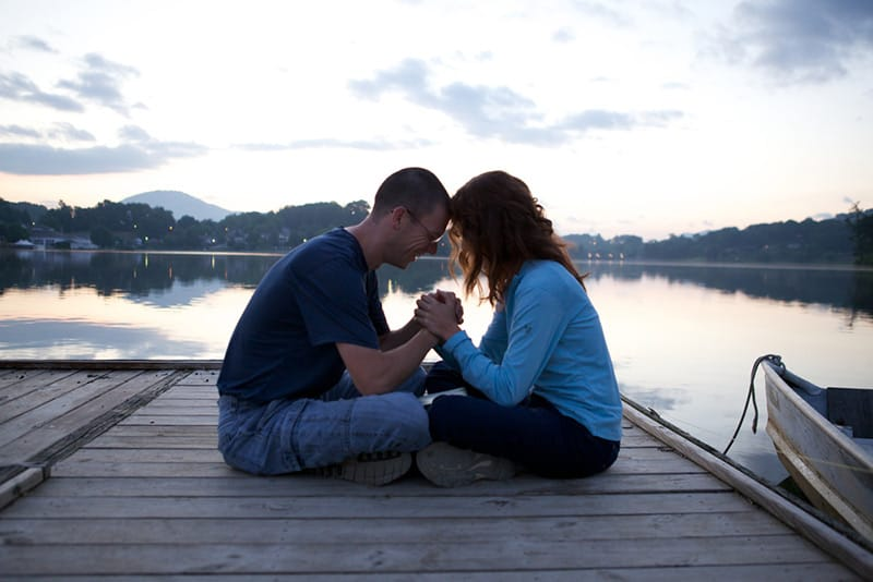 Couple praying while sitting on the dock by the lake