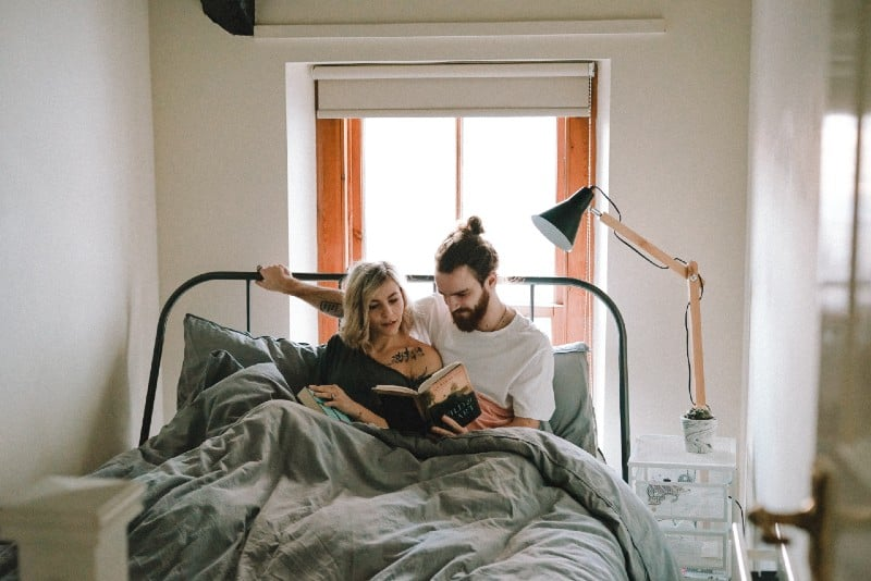 woman and man reading book in bed