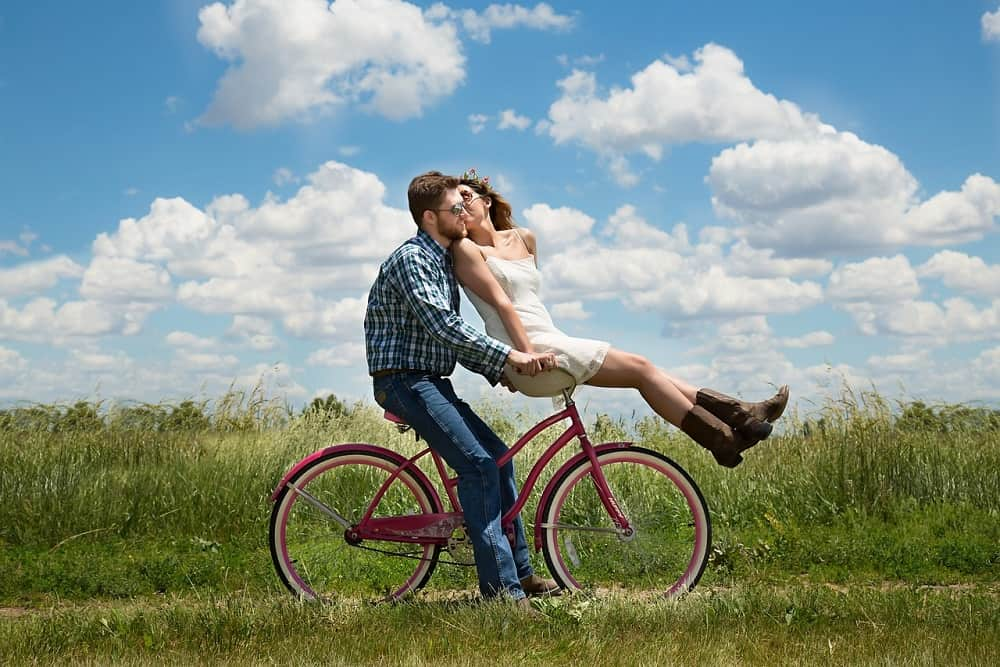 woman kissing the man while they are riding a bike
