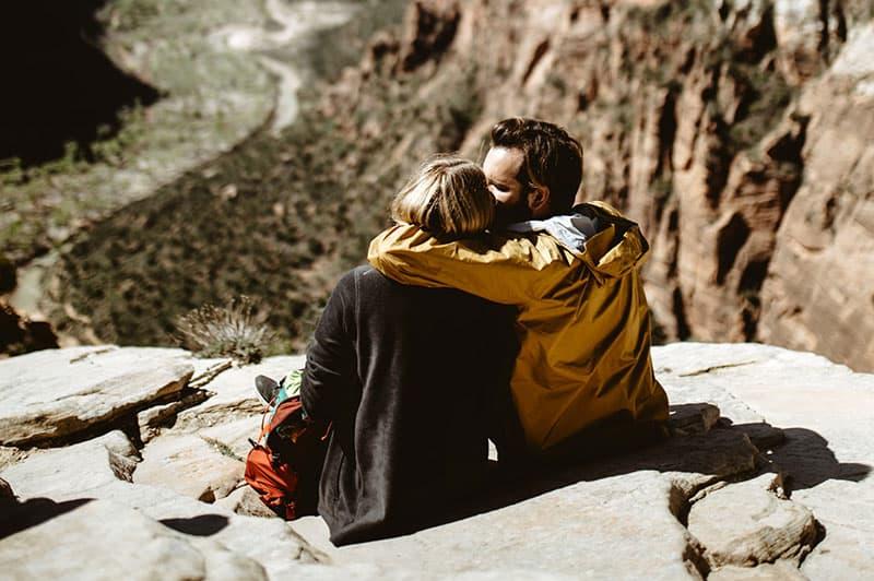 couple sitting on rocky ledge of mountain