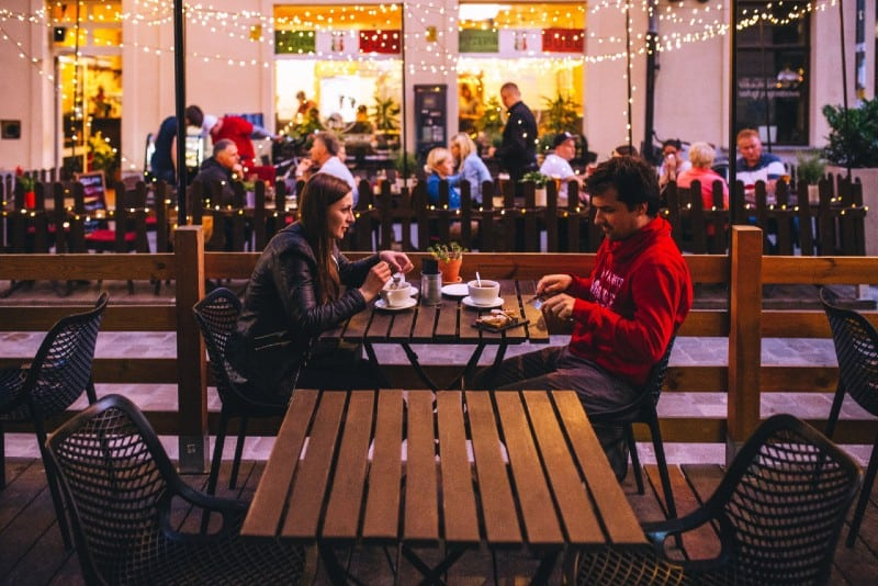 man and woman drinking coffee and sitting at table outdoor
