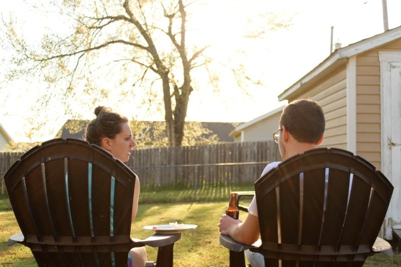 woman and man sitting on chairs backyard