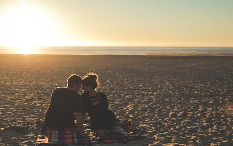couple sitting next to each other on the empty beach at sunset time