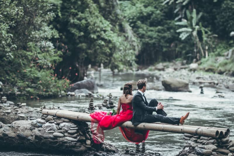 couple sitting on wooden bridge in forest