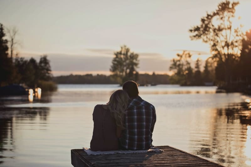 man and woman sitting on dock during golden hour