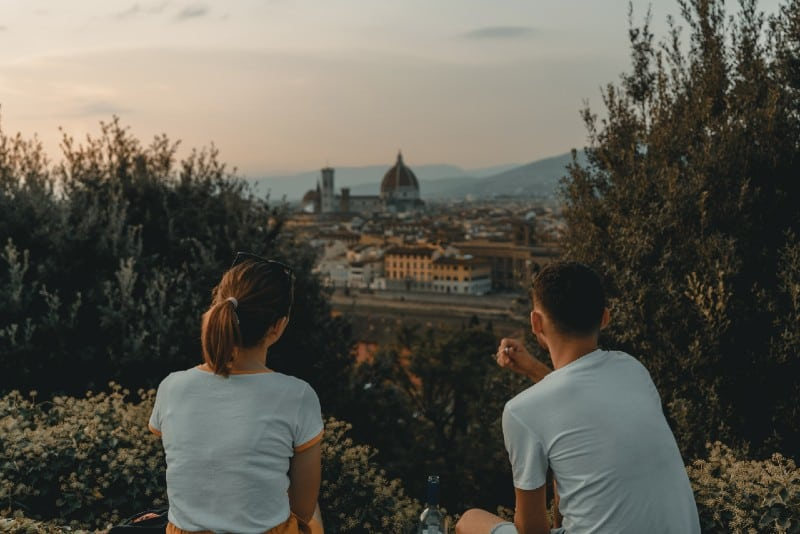 woman and man wearing white shirts and watching the city
