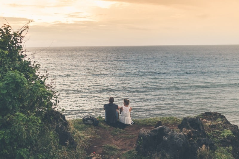 man and woman sitting on ground looking at sea