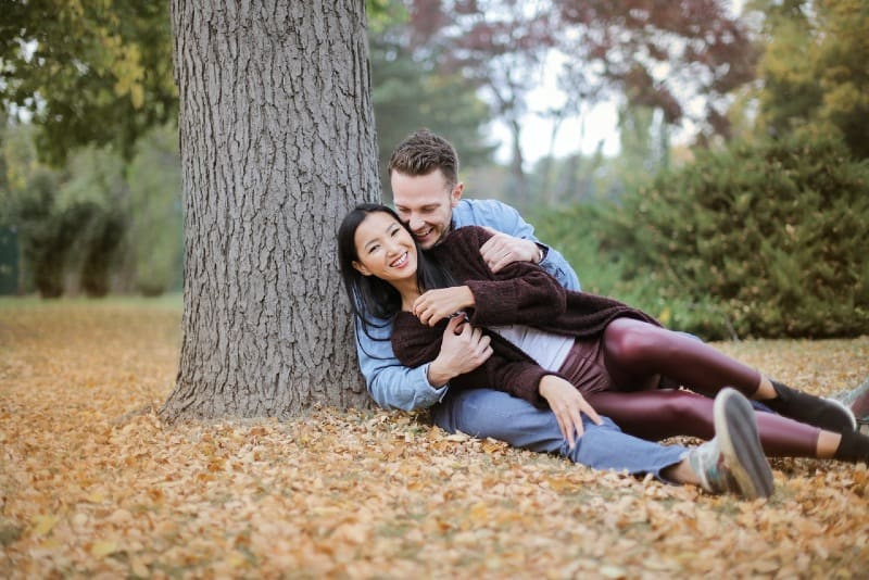 smiling man and woman sitting on leaves under the tree