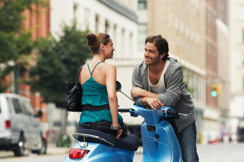 couple sitting on moped and talking