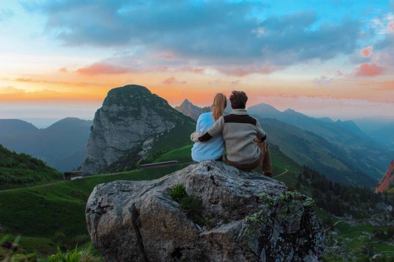 couple sitting on top of hill