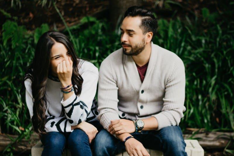 smiling woman sitting beside man