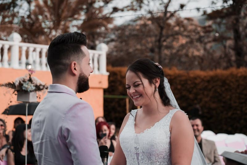 groom and bride smiling and standing outdoor
