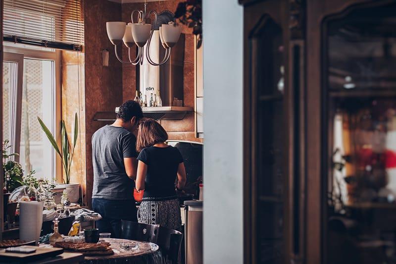 couple standing in the kitchen preparing breakfast