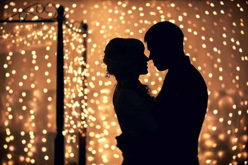 couple standing in the room of garlands of lights