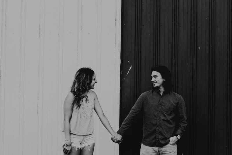 man and woman standing near wall and holding hands