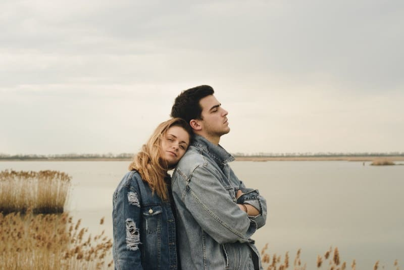 woman in denim jacket leaning on man's shoulder near water