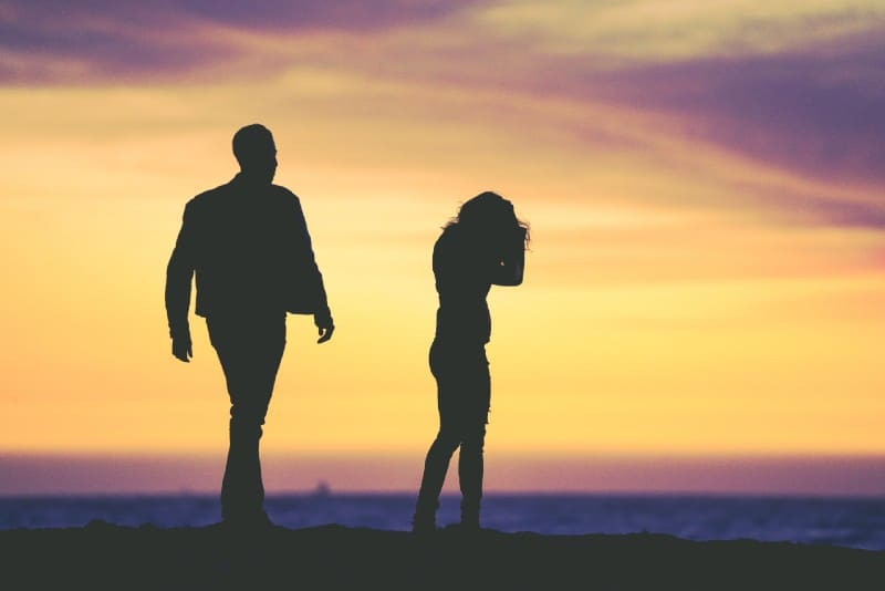 silhouette of man and woman standing on beach